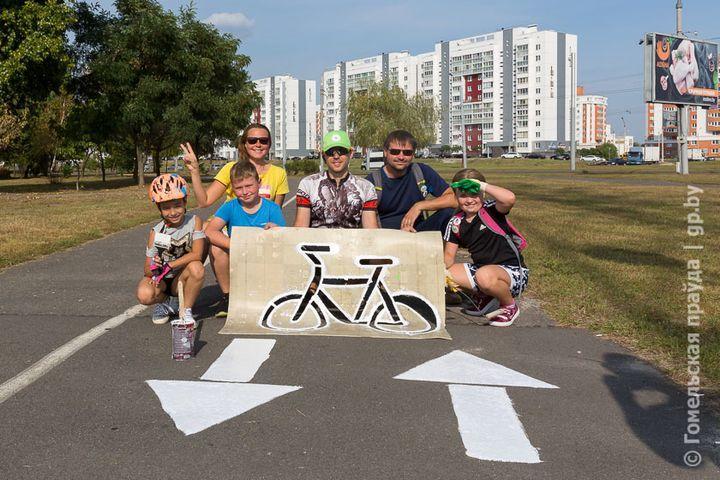 Маленькие велосипедисты и их родители обновляют разметку на велодорожках в Гомеле