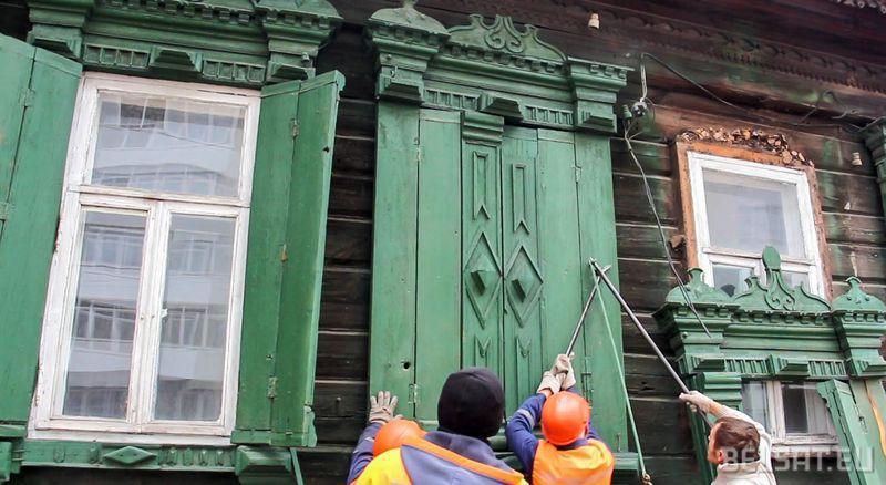 Рабочие разбирают деревянный дом